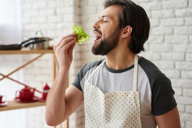 O homem alegre no avental prova as folhas da alface na cozinha.
