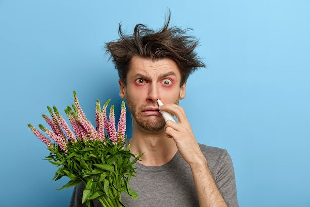 O homem alérgico tem penteado bagunçado, olhos vermelhos com coceira, segura a planta que causa espirros ou rigidez, sofre de sintomas desagradáveis, faz tratamento em casa, fica encostado na parede azul. secreção nasal