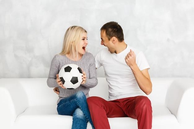 O homem animado assistir uma bola de futebol perto de uma mulher no sofá