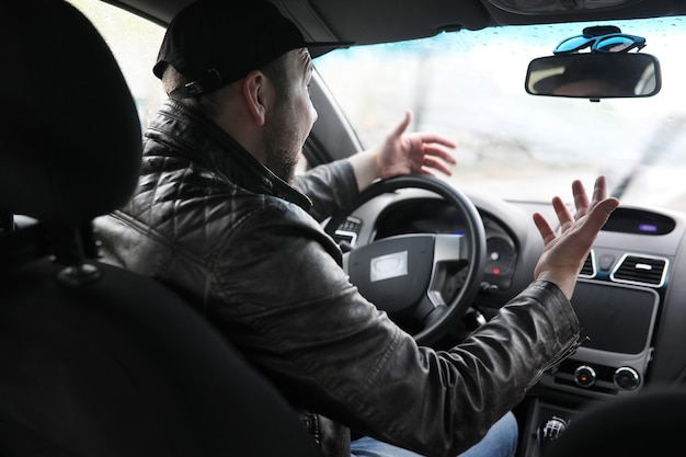 O homem ao volante de um carro enquanto dirige em um dia chuvoso