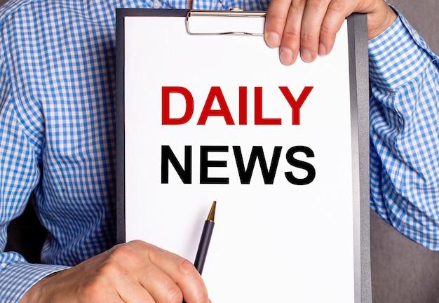 O homem aponta com uma caneta o texto notícias diárias em um lençol branco.
