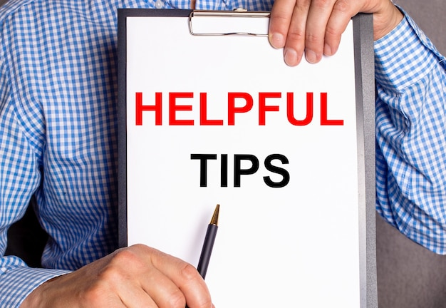 O homem aponta com uma caneta para o texto dicas úteis em uma folha branca