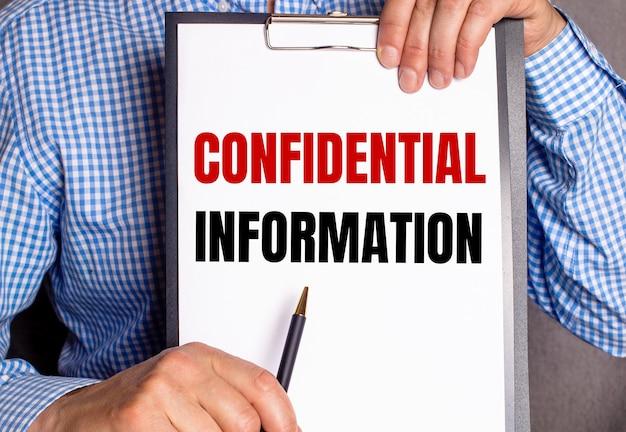 O homem aponta com uma caneta para o texto informações confidenciais em uma folha branca.