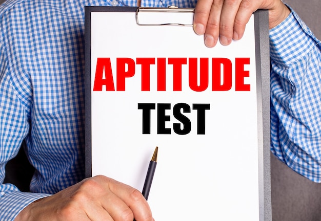O homem aponta com uma caneta para o texto teste de aptidão em um lençol branco.