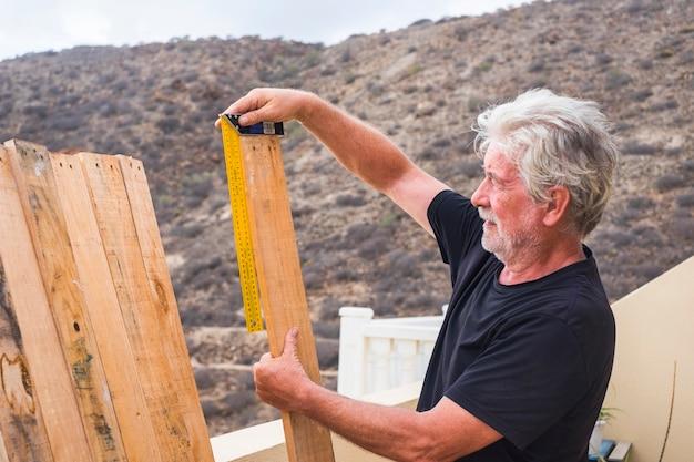 O homem aposentado adulto trabalha ao ar livre como um carpinteiro medindo as dimensões de uma mesa de madeira - construindo e consertando ou restaurando nas atividades de lazer - estilo de vida da sociedade de prata