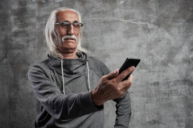 O homem aposentado caucasiano grisalho envelhecido parece surpreendido na tela do telefone móvel. avô em copos com bigode, dominando a tecnologia moderna.