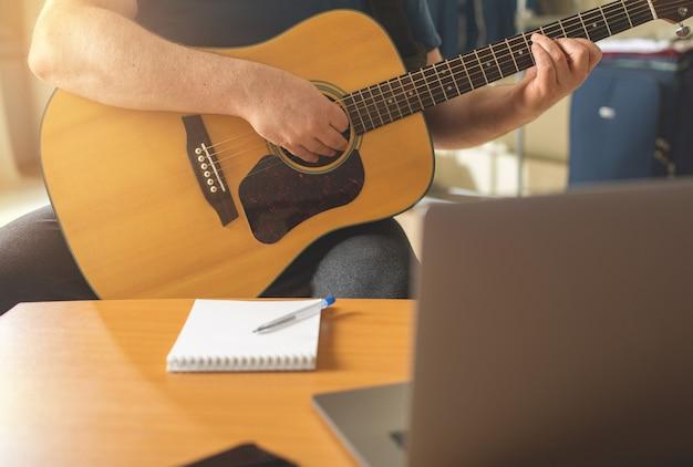 O homem aprende a tocar violão por meio de vídeo-aulas online.