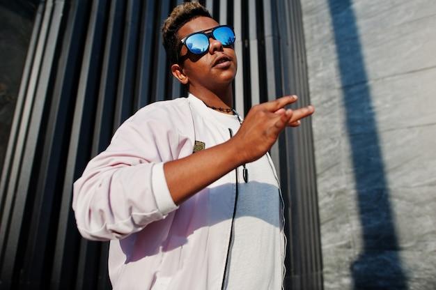 O homem árabe à moda hipster em óculos de sol posou ao ar livre na rua ao pôr do sol contra a parede cinza, mostra o gesto com a mão legal.