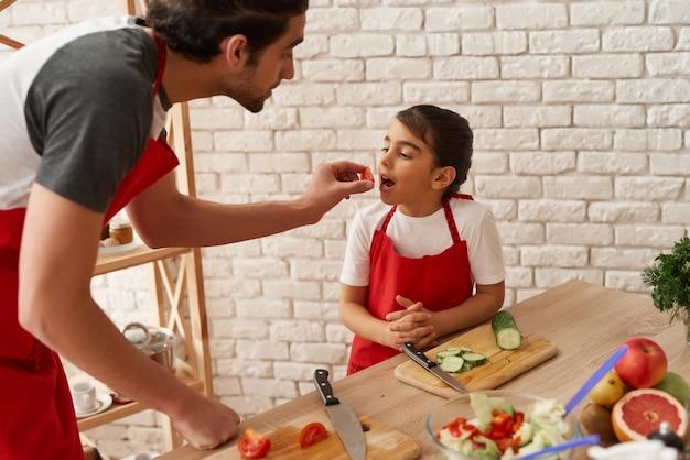 O homem árabe está alimentando a filha pequena com tomate.