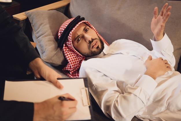 O homem árabe está deitado na cama por um psicólogo.