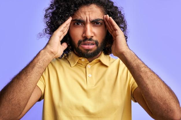 O homem árabe está tentando se lembrar de segurar as mãos na têmpora, pensando