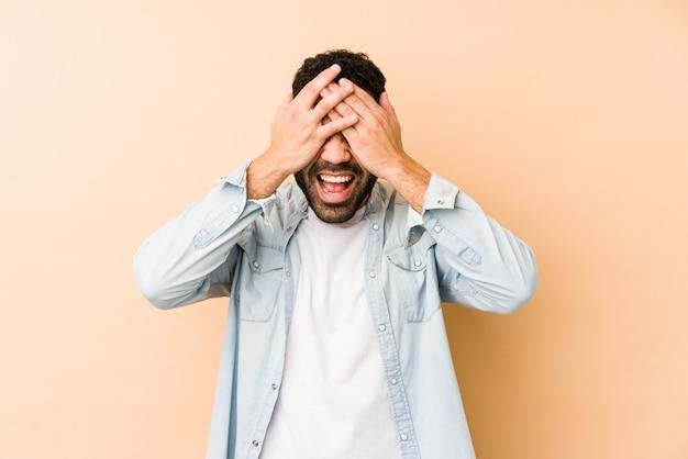 O homem árabe novo da raça misturada isolado cobre os olhos com as mãos, sorri amplamente esperando uma surpresa.