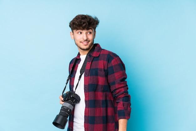 O homem árabe novo do fotógrafo isolado olha de lado o sorriso, alegre e agradável.