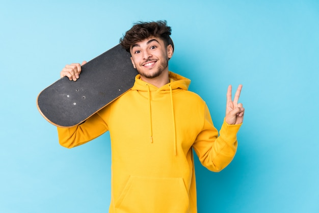 O homem árabe novo do skatista isolou alegre e despreocupado mostrando um símbolo de paz com os dedos.