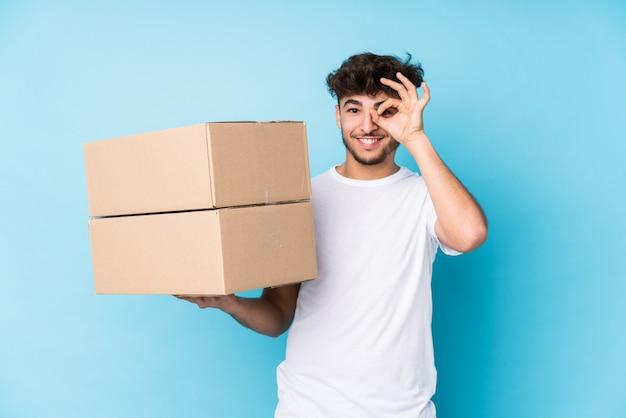 O homem árabe novo que guarda caixas isolou entusiasmado mantendo o gesto aprovado no olho.