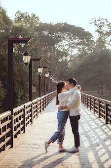 O homem asiático abraça a namorada na ponte com a lâmpada o tempo todo. eles serão beijarão juntos.