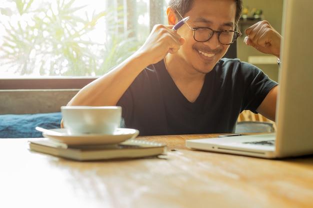 O homem asiático com mãos levantadas portátil comemora acima o sucesso em grandes notícias.