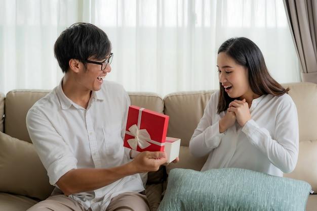 O homem asiático dá à mulher uma caixa de presente vermelha.