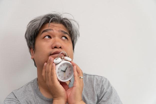 O homem asiático de meia-idade está segurando um despertador branco e seu rosto mostrou tédio e se sentindo mal,