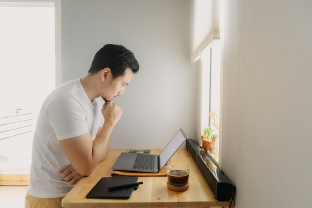 O homem asiático do freelancer está pensando e está trabalhando em seu portátil. conceito de trabalhos criativos freelance.