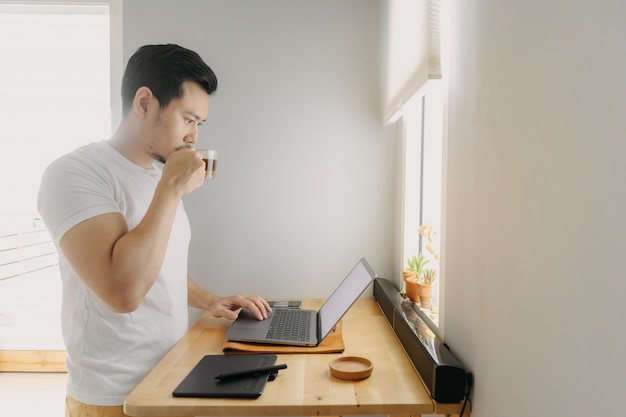 O homem asiático do freelancer está pensando e está trabalhando em seu portátil.