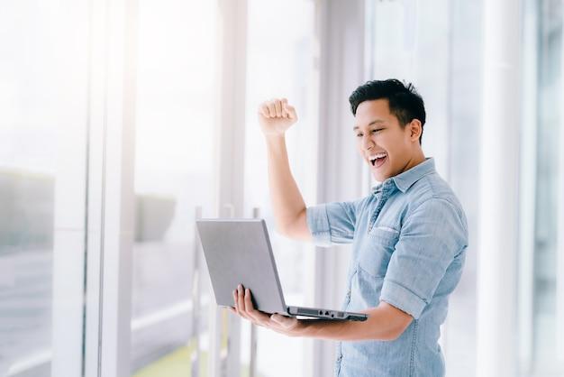 O homem asiático entusiasmado que guarda o portátil comemora o sucesso ou a realização.
