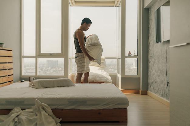 O homem asiático está limpando seu quarto com a luz morna do verão.