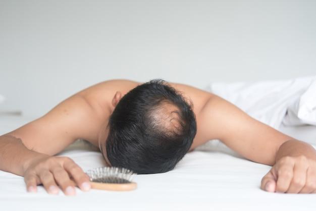 O homem asiático está preocupado com o problema da queda de cabelo na cama em casa.