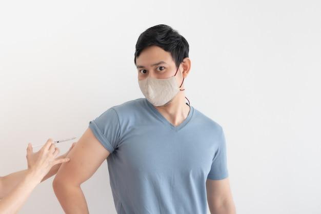 O homem asiático está recebendo uma vacina para proteção contra o vírus.