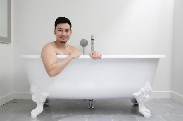 O homem asiático está se divertindo em uma banheira branca.