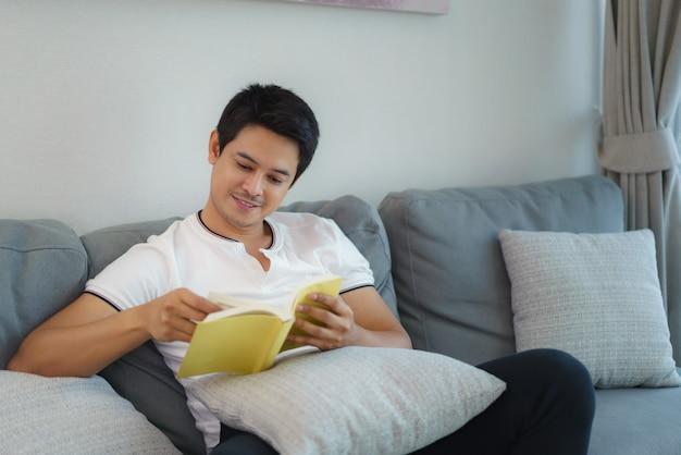 O homem asiático está sentado lendo livros, descansando no sofá da sala de estar da casa.