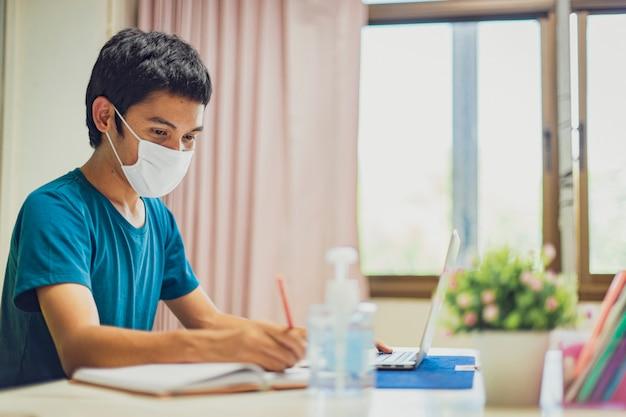 O homem asiático está trabalhando em casa durante o coronavirus ou o covid-19. usando uma máscara facial para proteger contra o coronavírus.