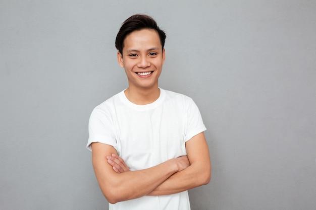 O homem asiático feliz que está com braços cruzou-se sobre a parede cinzenta.