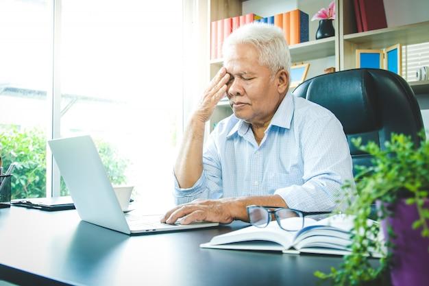 O homem asiático idoso estava sentado no escritório. ele está estressado e está doente.
