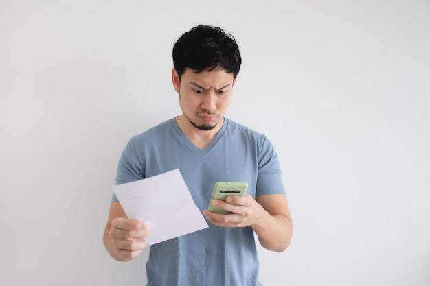 O homem asiático leva a sério a conta e o smartphone na parede isolada.