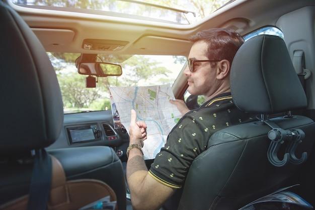 O homem asiático motorista bonito senta-se na mão do carro segura o mapa e vira o corpo para trás com um sorriso e o polegar.