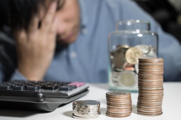 O homem asiático na camisa azul é forçado sobre o dinheiro no quarto.