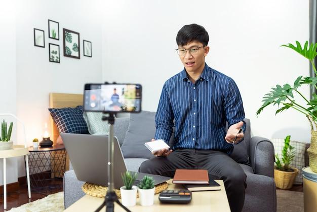 O homem asiático nos fones de ouvido que escreve notas no caderno que olha o curso video do webinar estuda através do estudo em linha da leitura do portátil em casa, conceito do ensino eletrónico.