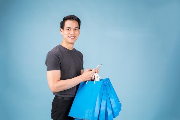 O homem asiático novo com sacos de compras está usando um telefone celular e está sorrindo ao fazer o shopping