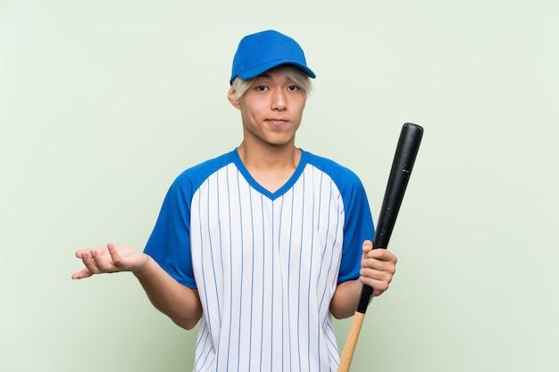 O homem asiático novo que joga beisebol sobre o fundo verde isolado que faz dúvidas gesticula ao levantar os ombros