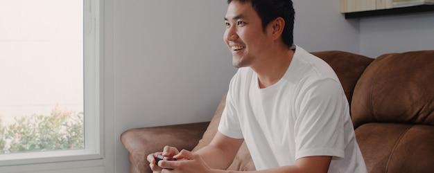 O homem asiático novo que usa o manche que joga os jogos video na televisão na sala de visitas, sentimento masculino feliz usando relaxa o tempo que encontra-se no sofá em casa. os homens jogam jogos relaxam em casa.