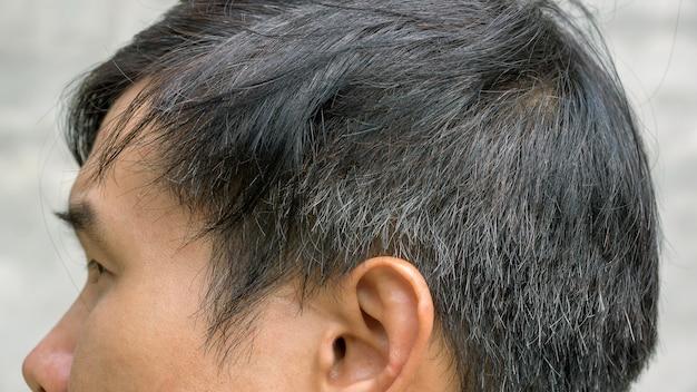 O homem asiático novo tem um cabelo cinzento.