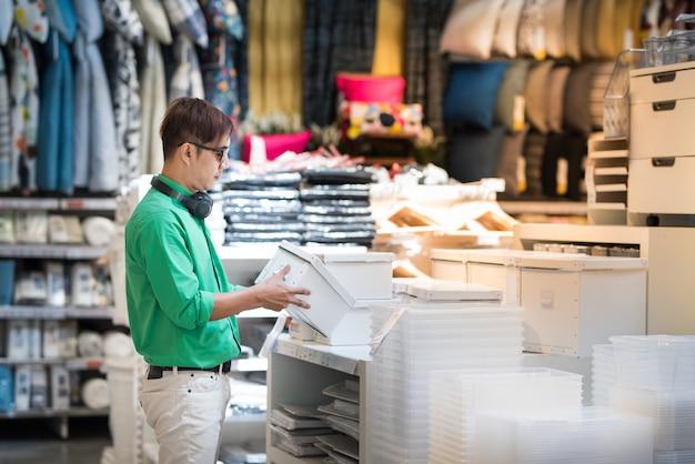O homem asiático novo vestido no estilo ocasional e veste vidros do olho que escolhem a caixa branca e faz shi