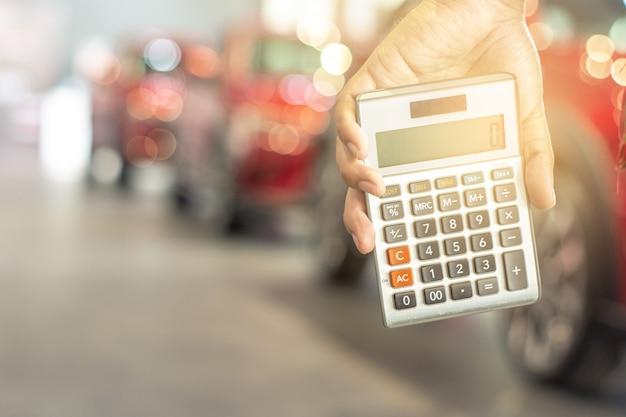 O homem asiático que guarda a calculadora para a finança do negócio na sala de exposições do carro borrou o fundo do bokeh.