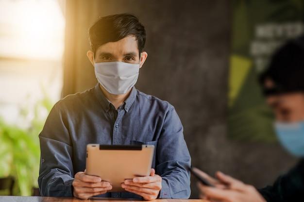 O homem asiático que usa a tabuleta em linha que trabalha uma máscara protetora vestindo protege o estilo de vida do vírus da corona novo normal, homem vive no café interno