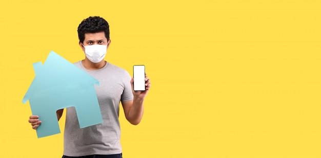 O homem asiático que veste uma mão da máscara segura o telefone inteligente e segura a casa de papel na parede amarela