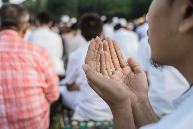 O homem asiático reza a oração de eid