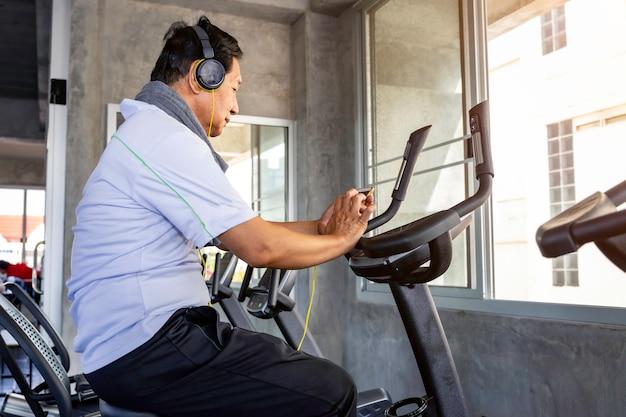 O homem asiático sênior no sportswear ouve música e cardio-bicicleta de treinamento no ginásio de fitness.