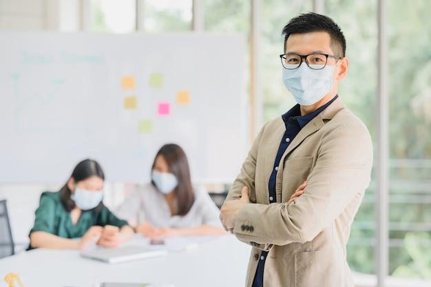 O homem asiático veste os braços eretos da máscara protetora cruzados com o confiante na sala de reuniões