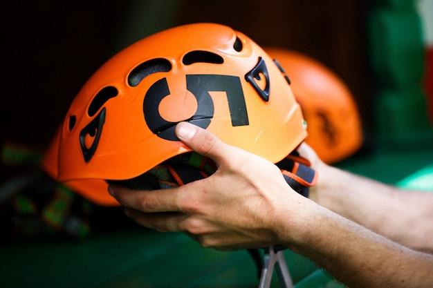 O homem assume um capacete de laranja com um número cinco